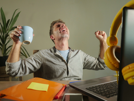 young satisfied and confident business man excited gesturing on victory as a winner working at home office with laptop computer on desk smiling happy in self employed and freelancer success