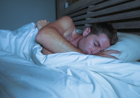 young attractive and handsome tired man on his 30s or 40s in bed sleeping shirtless peacefully and relaxed at apartment bedroom resting comfortable in  night lifestyle concept Stock Photo