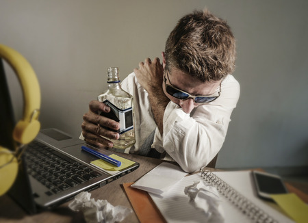 young sad and wasted messy business man working at laptop computer office desk drinking alcohol vodka bottle looking depressed and suffering problem in alcohol addiction and unhealthy lifestyle Stock Photo