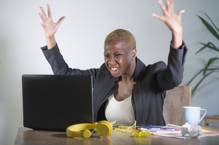 stressed and frustrated afro American black woman working overwhelmed and upset at office laptop computer desk gesturing angry in stress looking tired in business and work problem concept