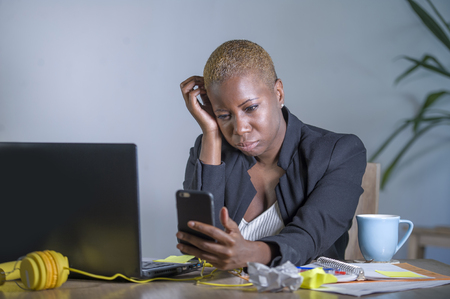 young desperate and stressed african american business woman working at laptop computer desk at office suffering stress problem using mobile phone overwhelmed in work crisis concept Stock Photo