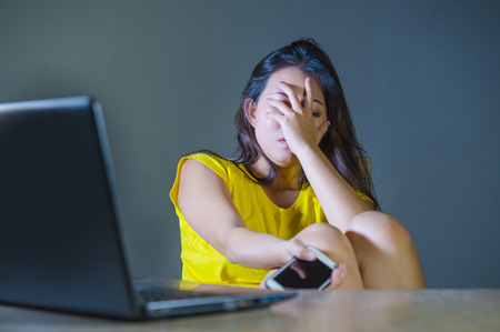 dramatic portrait of young sad and scared woman covering face with hands stressed and worried looking at laptop computer isolated on dark background in cyber bullying and internet problem