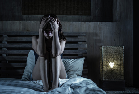 young sad and depressed Latin woman sitting on bed thoughtful and worried about problem or feeling sick and unwell covering face with hands in stress and depression feeling frustrated in pain