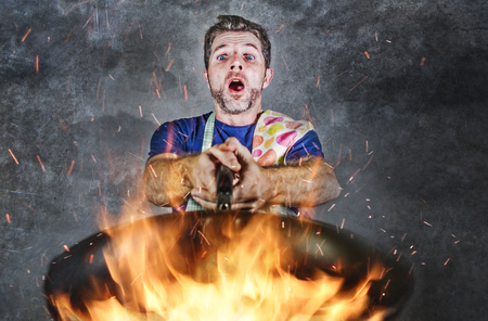 young attractive and shocked messy home cook man with apron holding pan in fire burning the food in kitchen disaster and unskilled and unexperienced terrible home cook at domestic cooking Foto de archivo