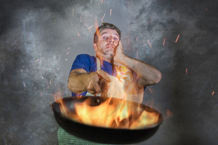 young attractive and shocked messy home cook man with apron holding pan in fire burning the food in kitchen disaster and unskilled and unexperienced terrible home cook at domestic cooking Stock Photo