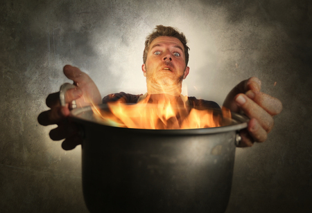 young attractive and shocked messy home cook man with apron holding cooking pot in fire burning the food in kitchen disaster and unskilled and terrible domestic husband chef work