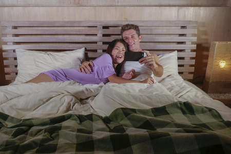young attractive and beautiful mix ethnicity happy couple with Asian Korean woman and Caucasian man lying in bed cuddling sweet using mobile phone together in love and relationship lifestyle concept