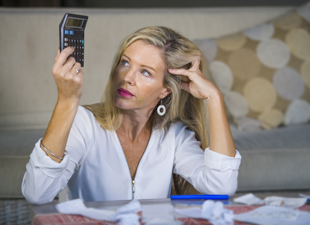 attractive worried and desperate blond woman calculating domestic money expenses doing paperwork and bank bills accounting with calculator suffering stress in financial problem and depression