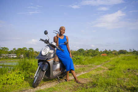 young beautiful and happy african american black woman posing cool on scooter motorbike at green field tropical landscape in adventure trip and summer holidays travel concept