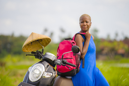 young beautiful and happy black afro american tourist woman with scooter motorbike looking to road map searching destination exploring fields in Asia holidays summer travel as digital nomad Stock Photo