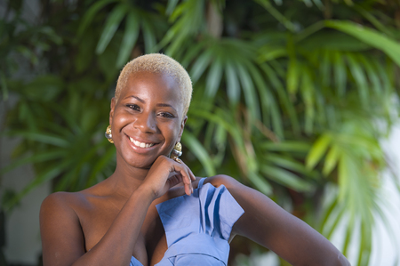 lifestyle portrait of young attractive and joyful black afro american woman smiling happy posing cheerful at home terrace with green plants background in  classy dress and  stylish hairstyle Archivio Fotografico