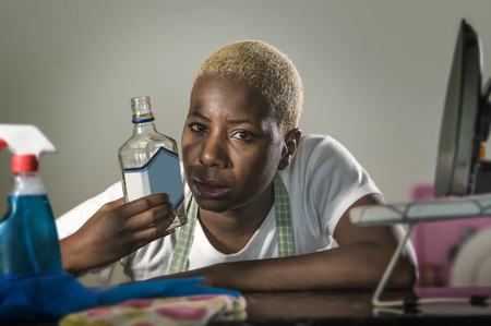 portrait of young wasted and drunk alcoholic black afro American housewife drinking alcohol bottle at home kitchen feeling desperate and sad in alcohol addiction and abuse problem