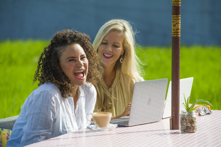 two happy female friends working outdoors at beautiful internet cafe with laptop computer , a caucasian woman and an afro mixed ethnicity girl enjoying together as digital nomad girlfriends