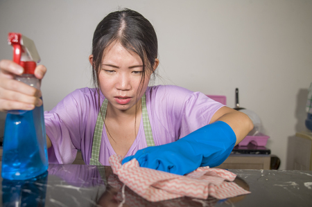 young pretty overworked and sad Asian Chinese service maid woman working domestic cleaning and washing home kitchen angry upset and frustrated in housework and housekeeping stress