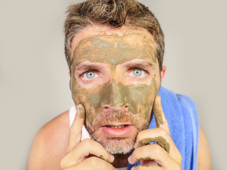 young messy funny man looking at himself horrified in bathroom mirror with green cream on his face applying beauty facial mask product feeling it disgusting and ugly in male cosmetic concept