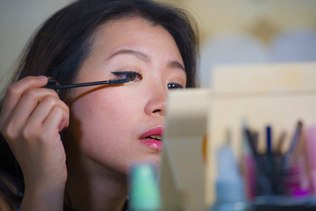 lifestyle natural portrait of young beautiful and happy Asian Korean woman at home applying make up eyelashes mascara looking in the mirror preparing for going out dating Stock Photo