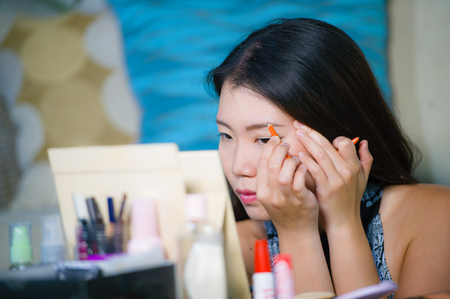 lifestyle natural portrait of young beautiful and happy Asian Korean woman at home applying make up profiling eyebrow with pencil looking in the mirror preparing for going out dating