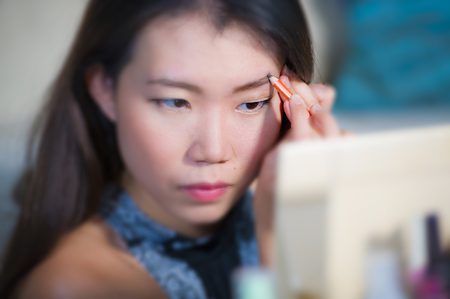 lifestyle natural portrait of young beautiful and happy Asian Korean woman at home applying make up profiling eyebrow with pencil looking in the mirror preparing for going out dating Stock Photo