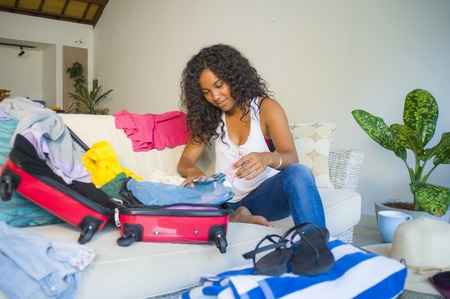young attractive and crazy happy black Afro American woman preparing clothes packing stuff in suitcase leaving for holidays trip excited and messy in travel vacations and tourism concept