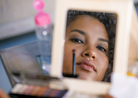 lifestyle mirror reflection portrait of young happy and beautiful hispanic woman applying face makeup using brush on eyelid putting eyeshadow in female beauty skin care and fashion concept
