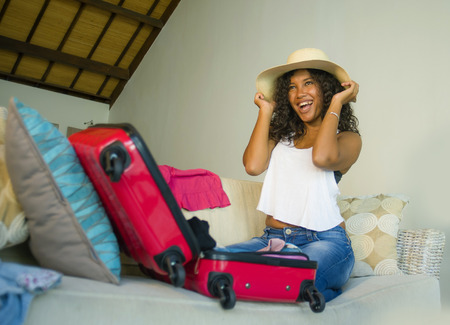 young attractive and crazy happy black African American woman in beach Summer hat preparing suitcase leaving for holidays trip excited and messy in travel vacations and tourism concept Stock Photo