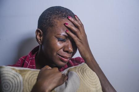 Lebensstil drinnen schattiges Porträt der jungen traurigen und depressiven schwarzen Afro-Amerikanerin, die zu Hause Boden sitzt und sich verzweifelt und besorgt fühlt, Schmerzen und Depressionen in dramatischem Licht leidend