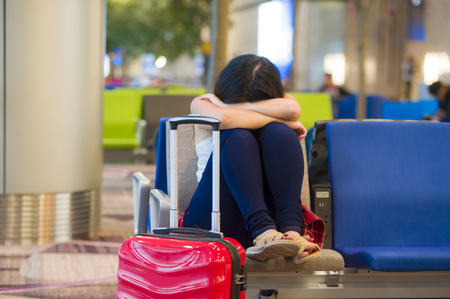 lifestyle portrait of young pretty tired and exhausted Asian Korean tourist woman in airport sleeping bored sitting at boarding gate hall waiting for delayed or canceled flight 免版税图像 - 106088786