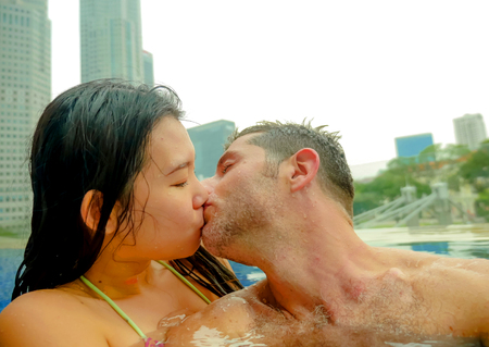 young happy and attractive playful couple taking selfie picture together with mobile phone at luxury urban hotel kissing at infinity pool enjoying holidays honeymoon in diversity ethnicity and love