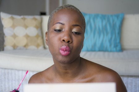lifestyle natural portrait of young happy and beautiful black afro American woman applying face makeup using brush on her lips looking herself in the mirror at home living room in beauty concept