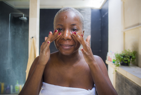 stile di vita naturale ritratto di giovane donna afroamericana nera attraente e felice a casa bagno guardando sullo specchio della toilette applicando il viso bellezza crema idratante gel sorridente fresco e allegro Archivio Fotografico
