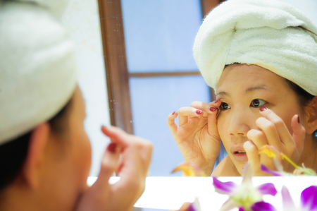 lifestyle fresh portrait of young happy and beautiful Asian Chinese woman at home or hotel bathroom wrapped in toilet towel applying makeup cheerful and natural in female beauty and skin care