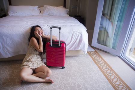 lifestyle natural portrait of young happy and beautiful Asian Korean tourist woman with travel suitcase arriving at five star hotel sitting on room floor staring excited and cheerful in holidays trip