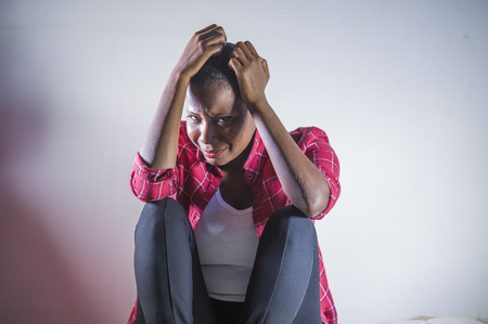 lifestyle indoors shady portrait of young sad and depressed black afro American woman sitting at home floor feeling desperate and worried suffering pain and depression in dramatic light