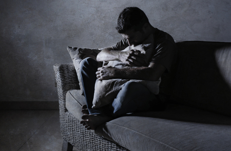 lifestyle dramatic light portrait of young sad and depressed man sitting at shady home couch in pain and depression feeling stressed and desperate crying alone suffering anxiety crisis