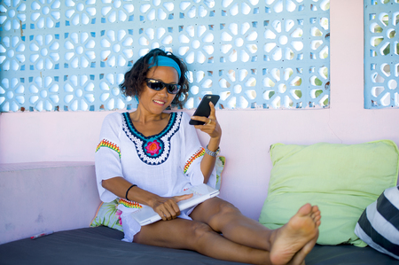 portrait of young attractive and happy hipster Asian woman having fun relaxed using internet mobile phone at relaxing outdoors bed cafe enjoying holidays trip chilling cool and cheerful