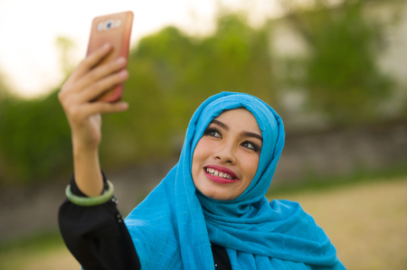 lifestyle portrait of young happy and beautiful tourist woman in muslim hijab head scarf taking selfie picture with mobile phone posing alone in holidays travel and smartphone technology concept Reklamní fotografie