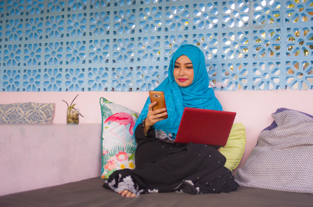 lifestyle outdoors portrait of young beautiful and happy woman in muslim hijab head scarf working with laptop computer and mobile phone networking running  internet business online from coffee shop 스톡 콘텐츠