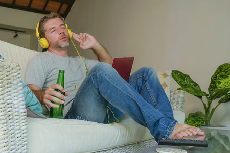 lifestyle indoors portrait of young happy relaxed and attractive man sitting at home sofa couch with headset and laptop listening to internet music online enjoying song relaxed drinking beer bottle 스톡 콘텐츠