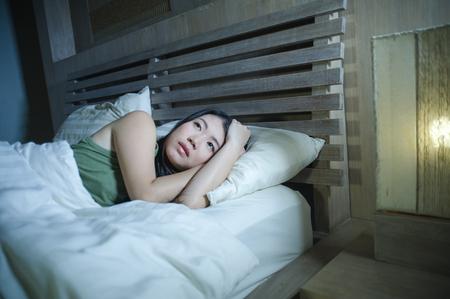 Retrato de noche de estilo de vida de joven hermosa mujer china asiática deprimida y triste que tiene insomnio acostado en la cama sin dormir sufrimiento ansiedad estrés y depresión problema pensando preocupado