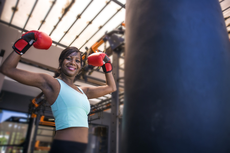 lifestyle indoors gym portrait of young attractive and beautiful black afro American woman training happy posing playful wearing boxing gloves at modern and cool combat fitness club