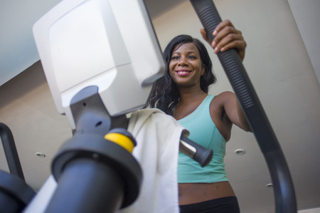 lifestyle gym portrait of young attractive and happy black African American woman training at fitness club smiling cheerful and sweaty during elliptical machine hard workout
