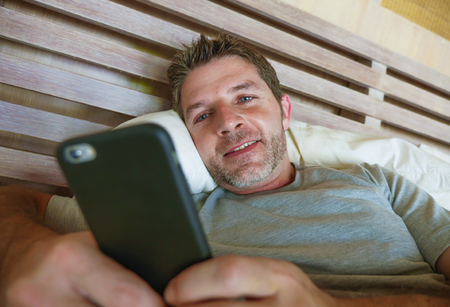 lifestyle indoors portrait of young happy and attractive man at home bedroom using internet social media app networking from bed smiling cheerful and relaxed in communication concept