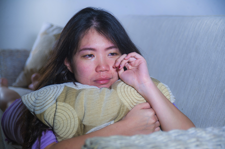 young sad and depressed Asian Korean woman at home sofa couch crying desperate and helpless suffering anxiety and depression feeling pain in relationship and lonely life problem concept