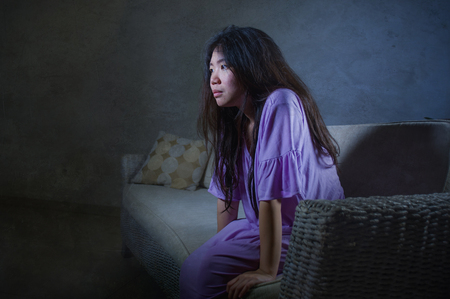 young sad and depressed Asian Chinese woman crying alone desperate sitting at home sofa ouch worried in pain and stress suffering depression and anxiety problem feeling lonely and helpless