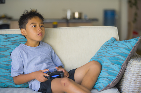lifestyle portrait of Latin young child 8 years old excited and happy playing video game online holding remote controller enjoying having fun sitting on couch in internet gaming kid addiction