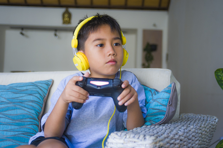lifestyle portrait of Latin young boy excited and happy playing video game online with headphones holding controller enjoying having fun sitting on couch in child gaming emotion and addiction