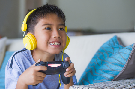 lifestyle portrait of young Latin little child excited and happy playing video game online with headphones holding controller having fun sitting on couch in gamer emotion and kid gaming addiction Foto de archivo