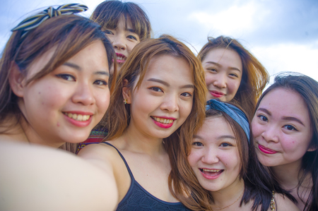 lifestyle beach portrait of Asian Korean and Chinese women, group of happy beautiful young girlfriends taking selfie picture together with mobile phone smiling cheerful enjoying girls holidays trip