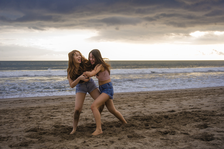 two happy and attractive young Asian Chinese women girlfriends or sisters having fun playing wrestling on sunset beach in beautiful light enjoying summer holidays travel together carefree Stockfoto