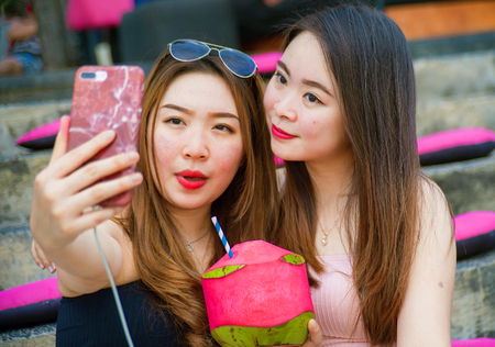 lifestyle outdoors portrait of young happy and beautiful Asian Chinese girls taking selfie picture with mobile phone enjoying holidays trip together sitting at  resort drinking tropical juice